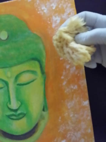 I'm using a small sponge to create texture around this painting of Buddha I'm working on.